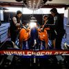 Team members work on the Lando Norris McLaren MCL34 in the pit garage