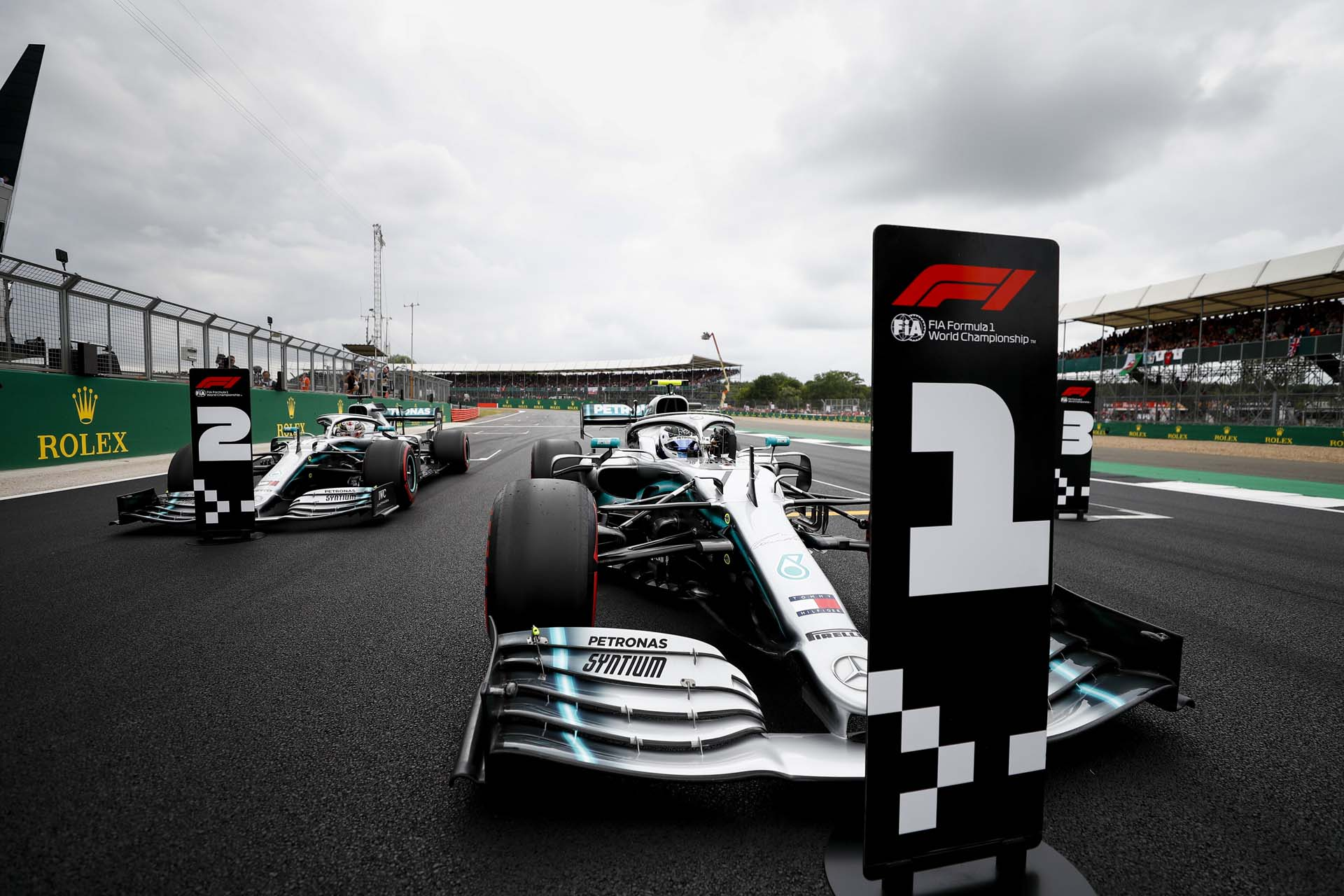 SILVERSTONE, UNITED KINGDOM - JULY 13: Pole Sitter Valtteri Bottas, Mercedes AMG W10 and Lewis Hamilton, Mercedes AMG F1 W10 drive into Parc Ferme during the British GP at Silverstone on July 13, 2019 in Silverstone, United Kingdom. (Photo by Glenn Dunbar / LAT Images)