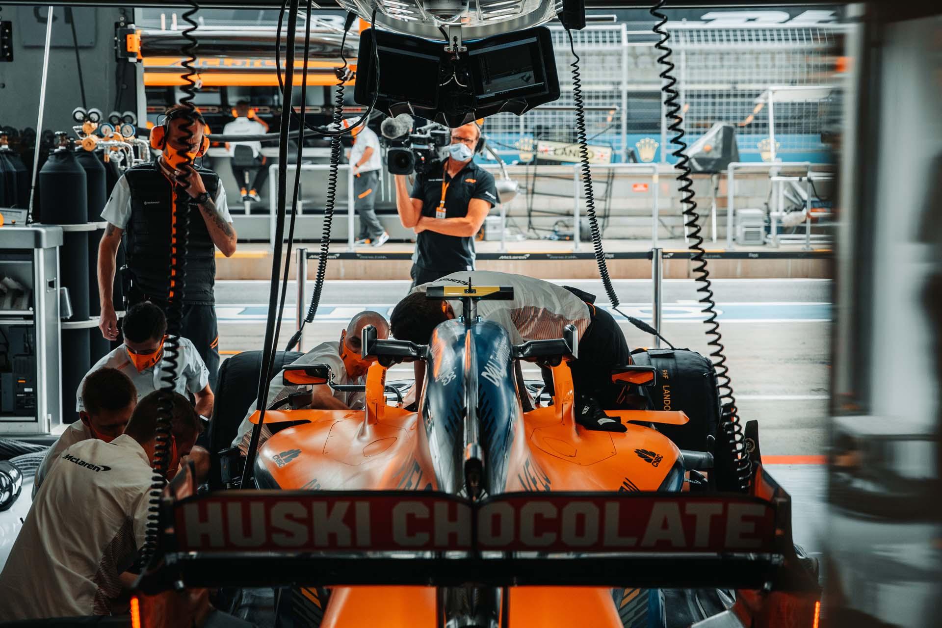 Mechanics at work on the car of Lando Norris, McLaren MCL35, in the garage