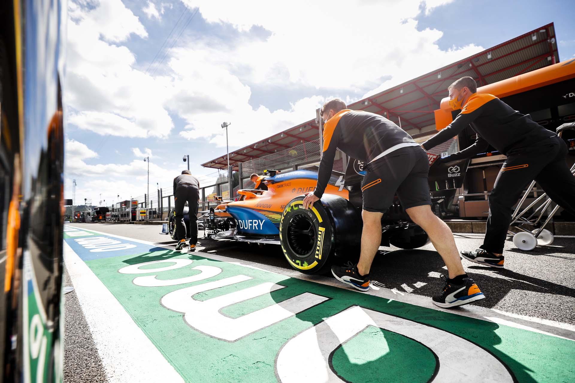 McLaren mechanics pushing the McLaren MCL35