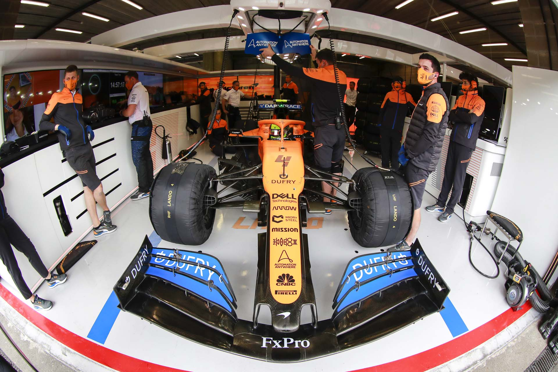 Mechanics and engineers in the garage with Lando Norris, McLaren MCL35