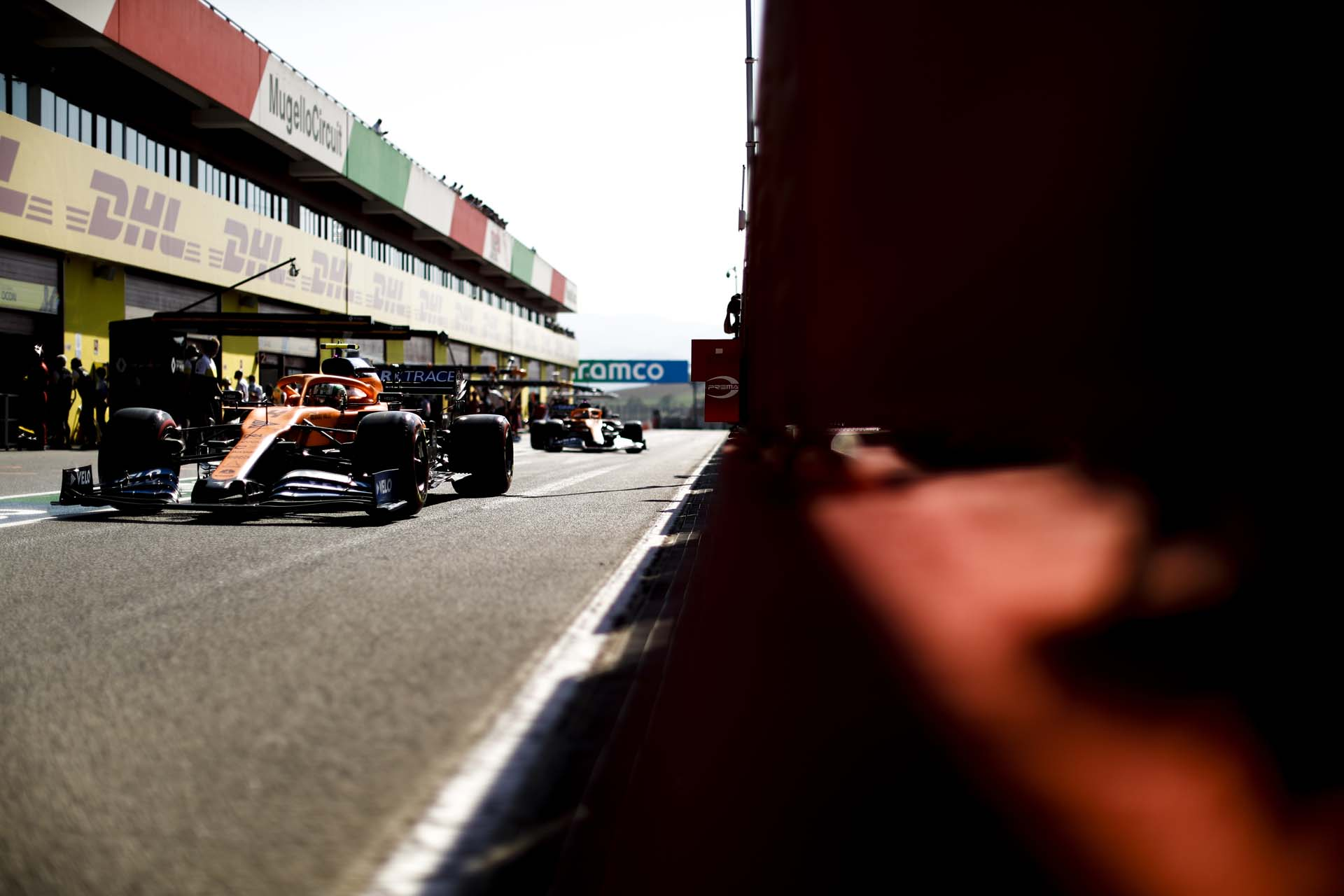 Lando Norris, McLaren MCL35, leads Carlos Sainz, McLaren MCL35, in the pit lane