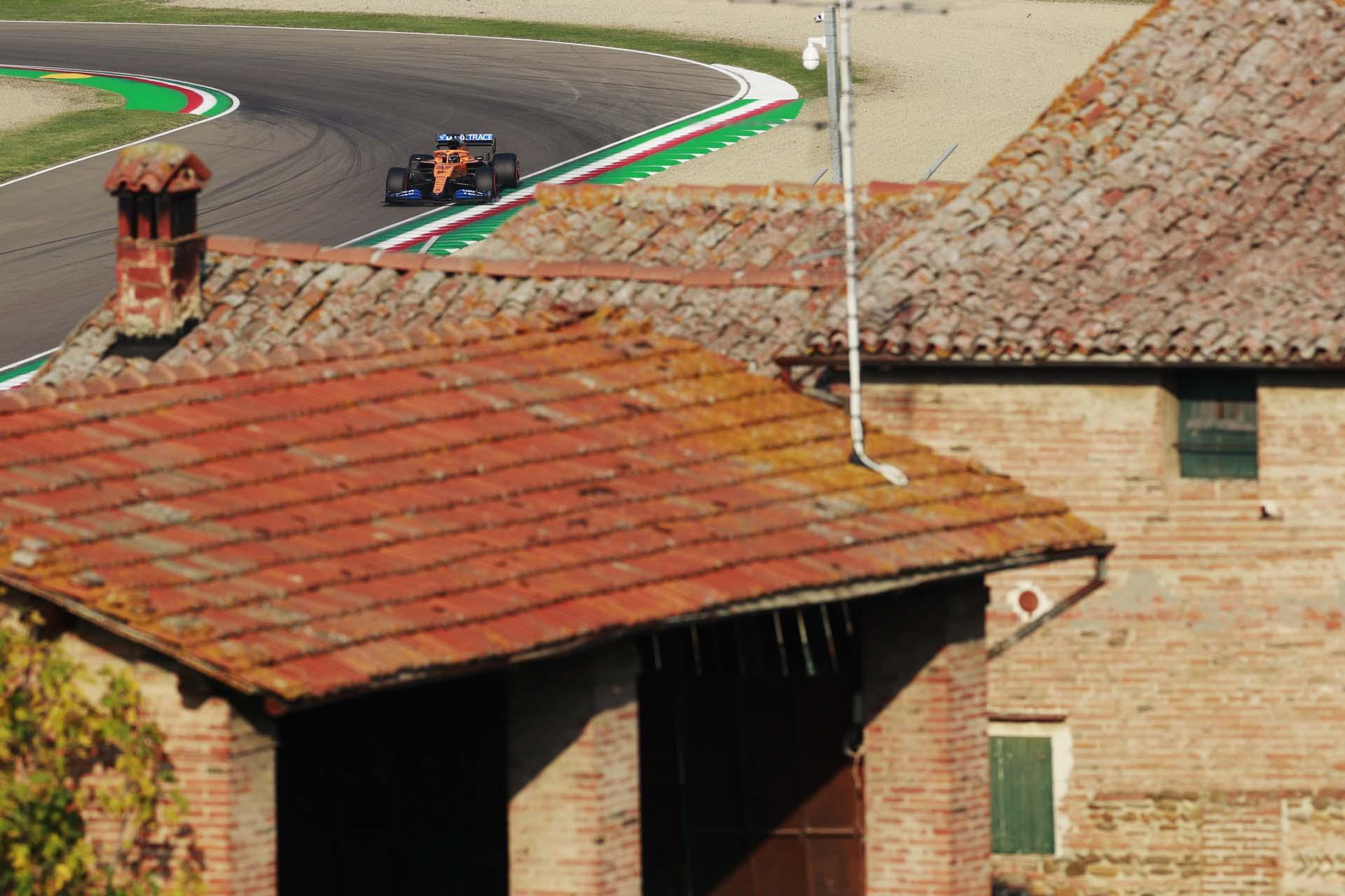 Carlos Sainz, McLaren MCL35, drives past some local architecture