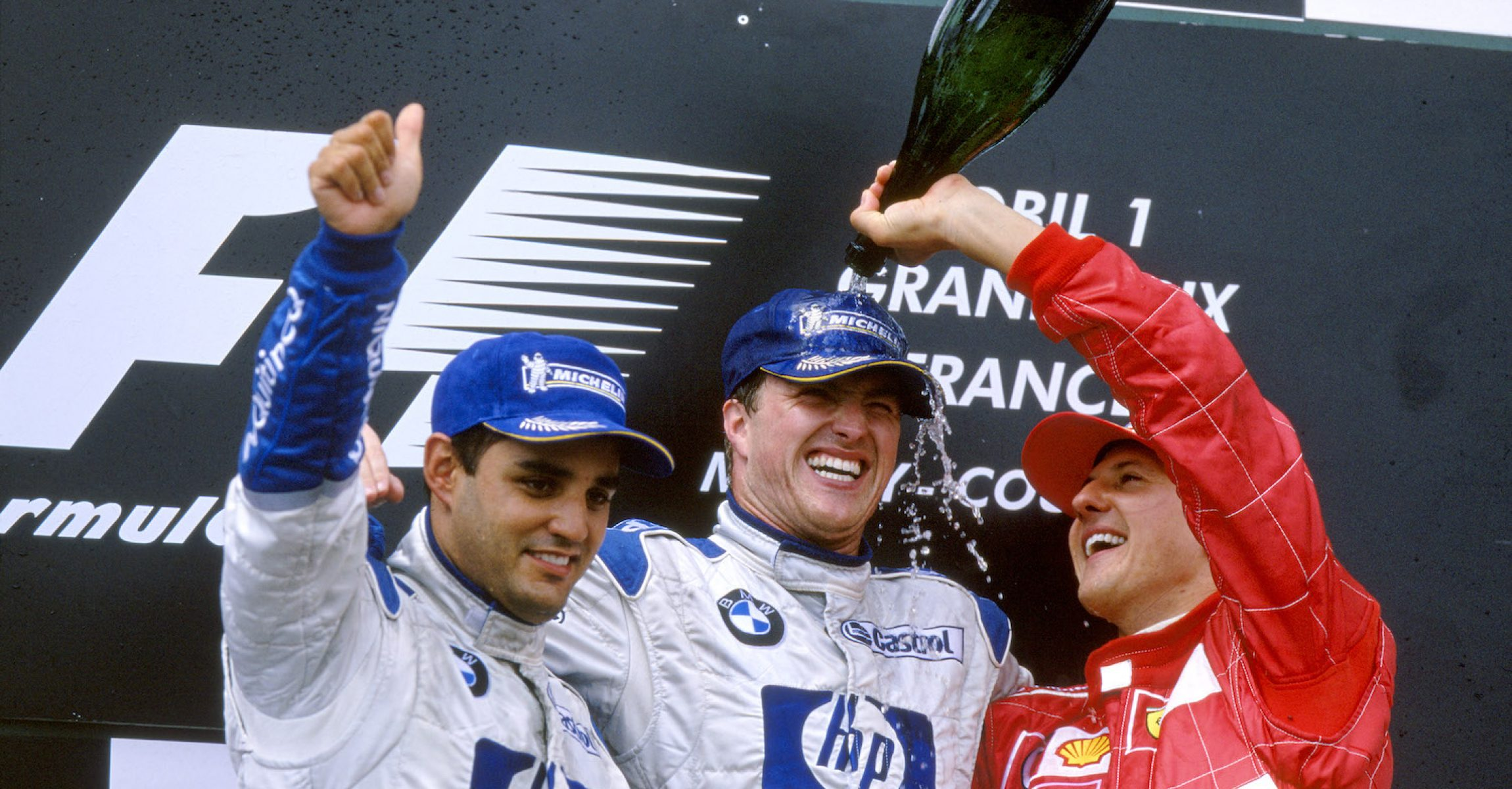 2003 French Grand Prix Magny Cours, France. 4th - 6th July 2003 Podium - Ralf Schumacher (Williams BMW) gets a champagne shower from thrid-placed brother Michael (Ferrari) as Juan Pablo Montoya (Williams BMW) celebrates another second place. World Copyright: Michael Cooper/LAT Photographic ref: 35mm Image 03 FRA 02