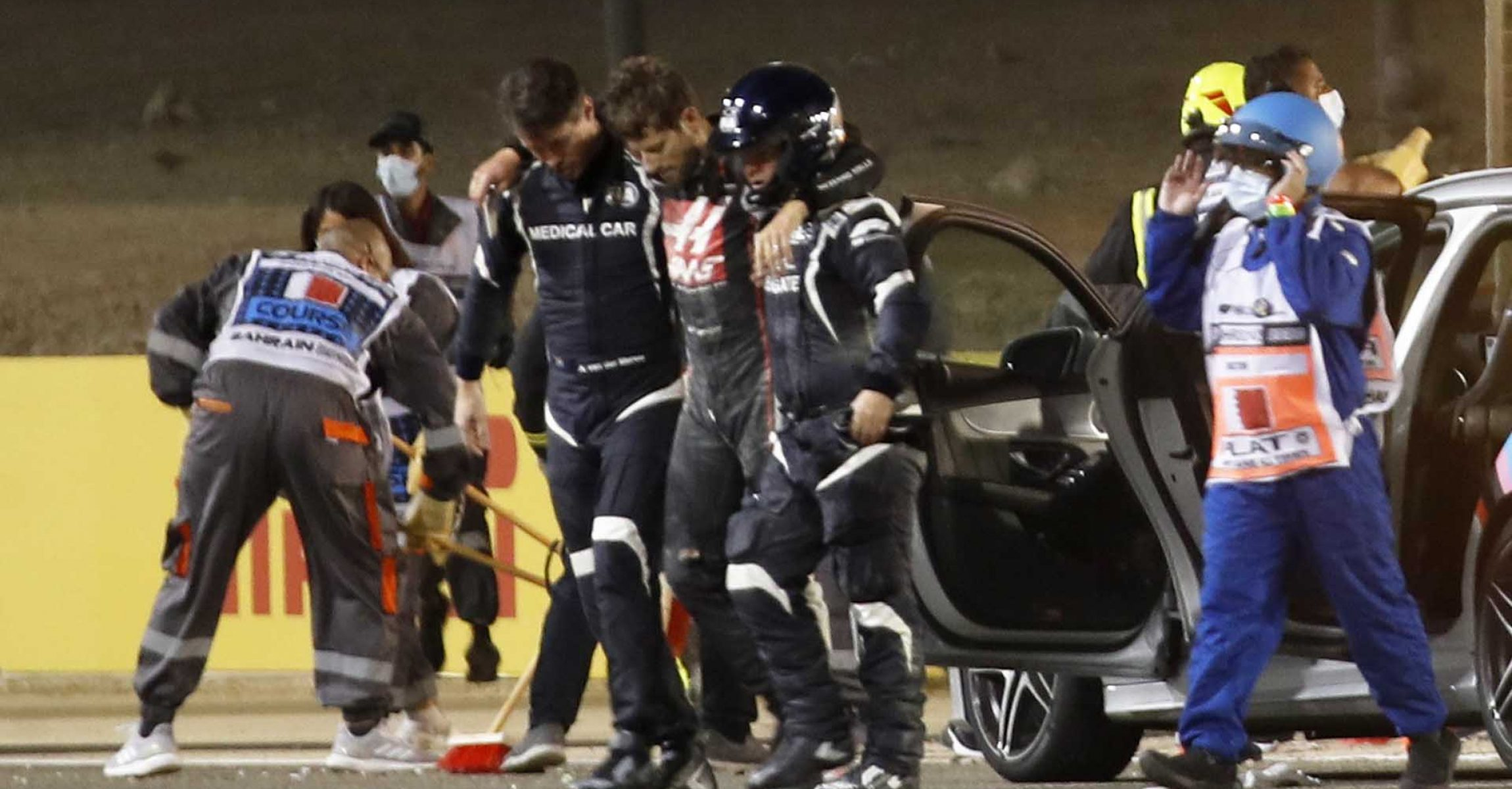 Formula One F1 - Bahrain Grand Prix - Bahrain International Circuit, Sakhir, Bahrain - November 29, 2020 Haas' Romain Grosjean is helped to walk away by medical officers after crashing out at the start of the race Pool via REUTERS/Hamad I Mohammed