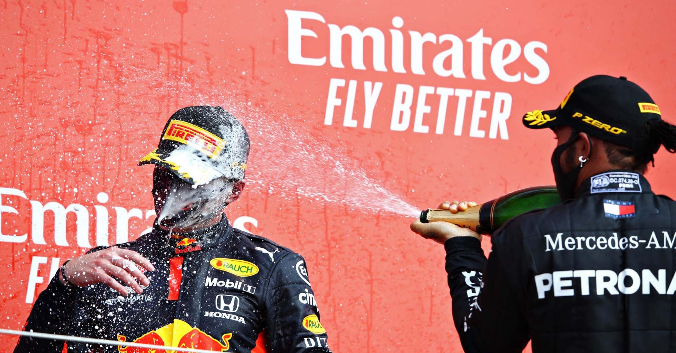 NORTHAMPTON, ENGLAND - AUGUST 09: Race winner Max Verstappen of Netherlands and Red Bull Racing and second placed Lewis Hamilton of Great Britain and Mercedes GP celebrate on the podium  during the F1 70th Anniversary Grand Prix at Silverstone on August 09, 2020 in Northampton, England. (Photo by Mark Thompson/Getty Images)