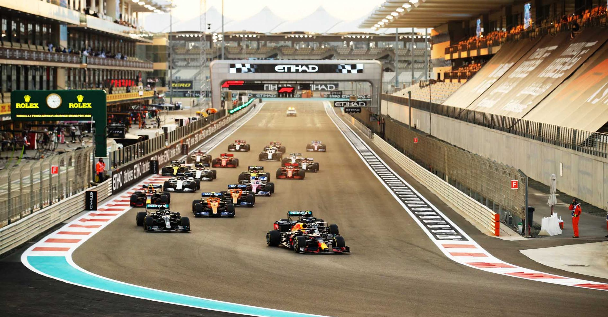 ABU DHABI, UNITED ARAB EMIRATES - DECEMBER 13: Max Verstappen of the Netherlands driving the (33) Aston Martin Red Bull Racing RB16 leads Lewis Hamilton of Great Britain driving the (44) Mercedes AMG Petronas F1 Team Mercedes W11 and Valtteri Bottas of Finland driving the (77) Mercedes AMG Petronas F1 Team Mercedes W11 into turn one at the start during the F1 Grand Prix of Abu Dhabi at Yas Marina Circuit on December 13, 2020 in Abu Dhabi, United Arab Emirates. (Photo by Bryn Lennon/Getty Images)