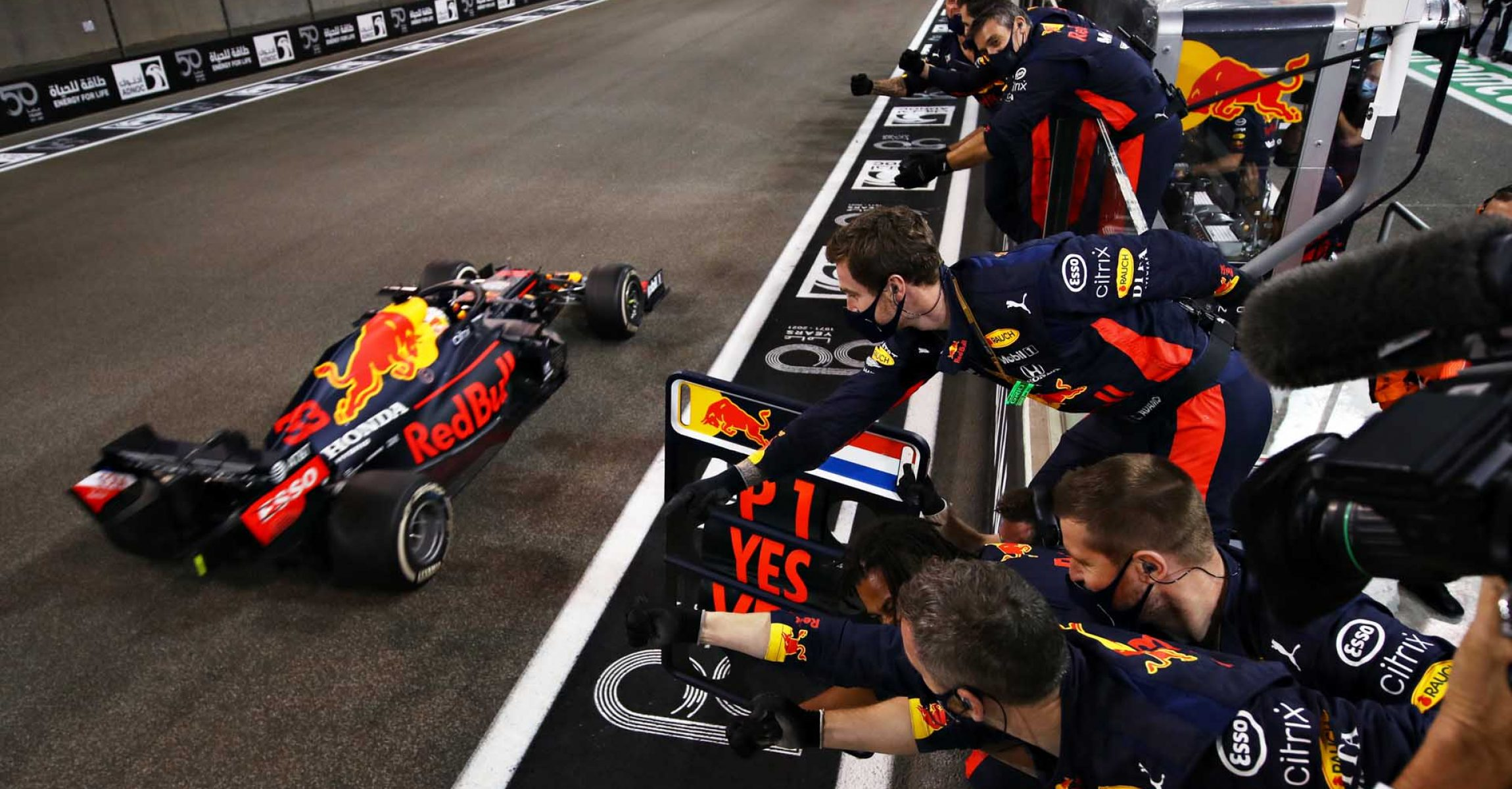 ABU DHABI, UNITED ARAB EMIRATES - DECEMBER 13: Race winner Max Verstappen of the Netherlands driving the (33) Aston Martin Red Bull Racing RB16 passes his team celebrating on the pitwall during the F1 Grand Prix of Abu Dhabi at Yas Marina Circuit on December 13, 2020 in Abu Dhabi, United Arab Emirates. (Photo by Mark Thompson/Getty Images)