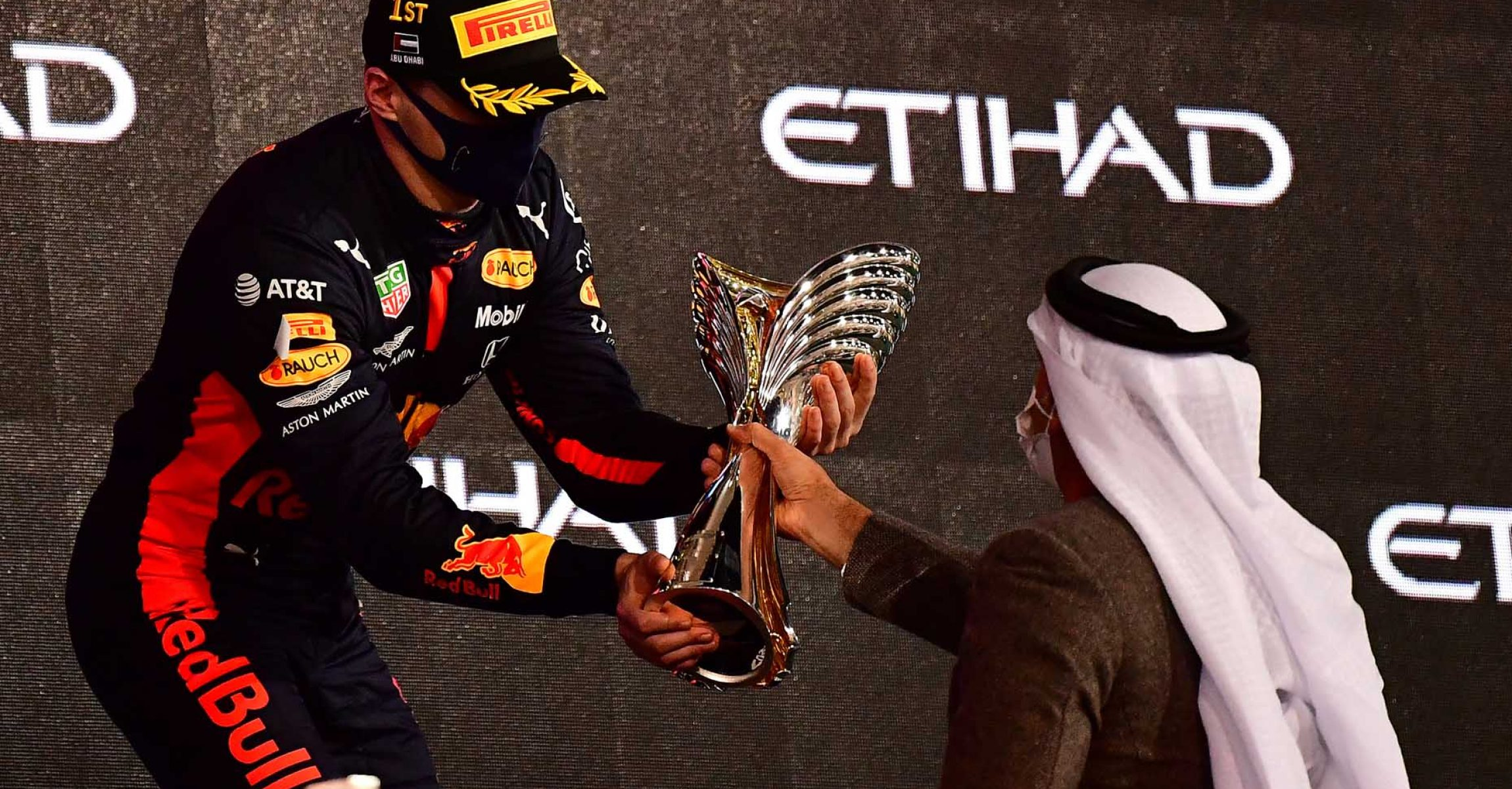 ABU DHABI, UNITED ARAB EMIRATES - DECEMBER 13: Race winner Max Verstappen of Netherlands and Red Bull Racing is presented with his trophy on the podium during the F1 Grand Prix of Abu Dhabi at Yas Marina Circuit on December 13, 2020 in Abu Dhabi, United Arab Emirates. (Photo by Giuseppe Cacace - Pool/Getty Images)