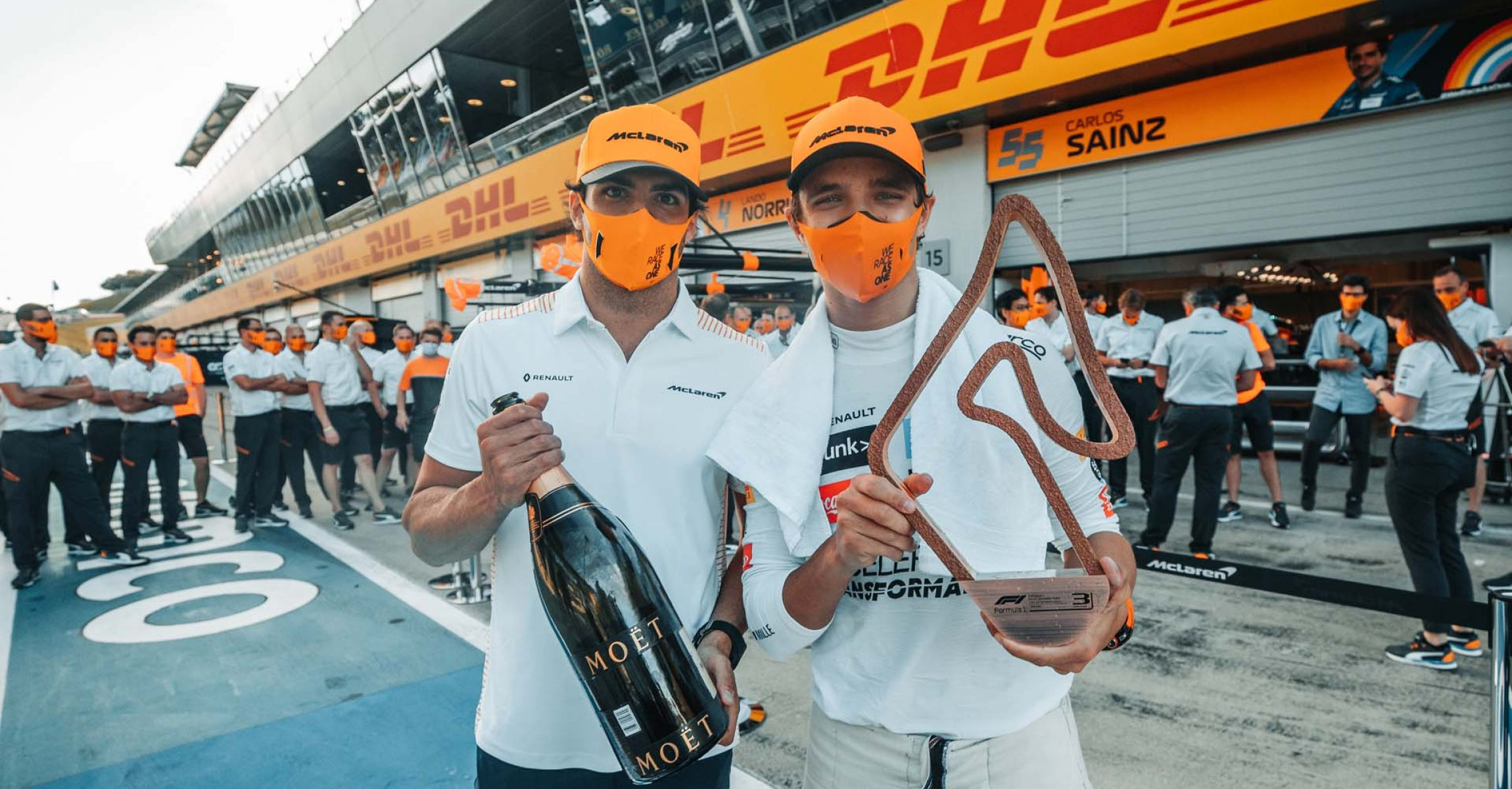 Lando Norris, McLaren, celebrates with Carlos Sainz, McLaren, champagne and his trophy after finishing on the podium