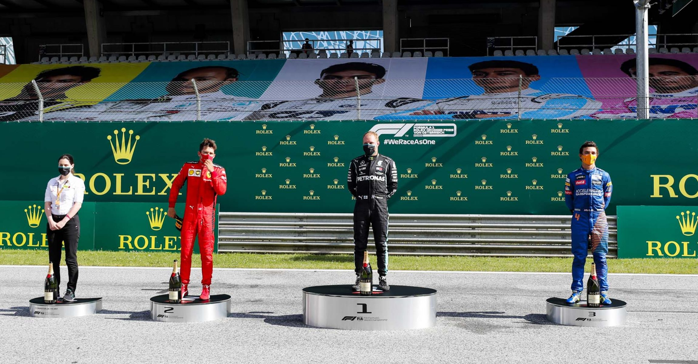 JULY 05: Mercedes Team Member, Charles Leclerc, Ferrari, race winner Valtteri Bottas, Mercedes-AMG Petronas F1 and Lando Norris, McLaren on the podium during the Austrian GP on Sunday July 05, 2020. (Photo by Steven Tee / LAT Images)