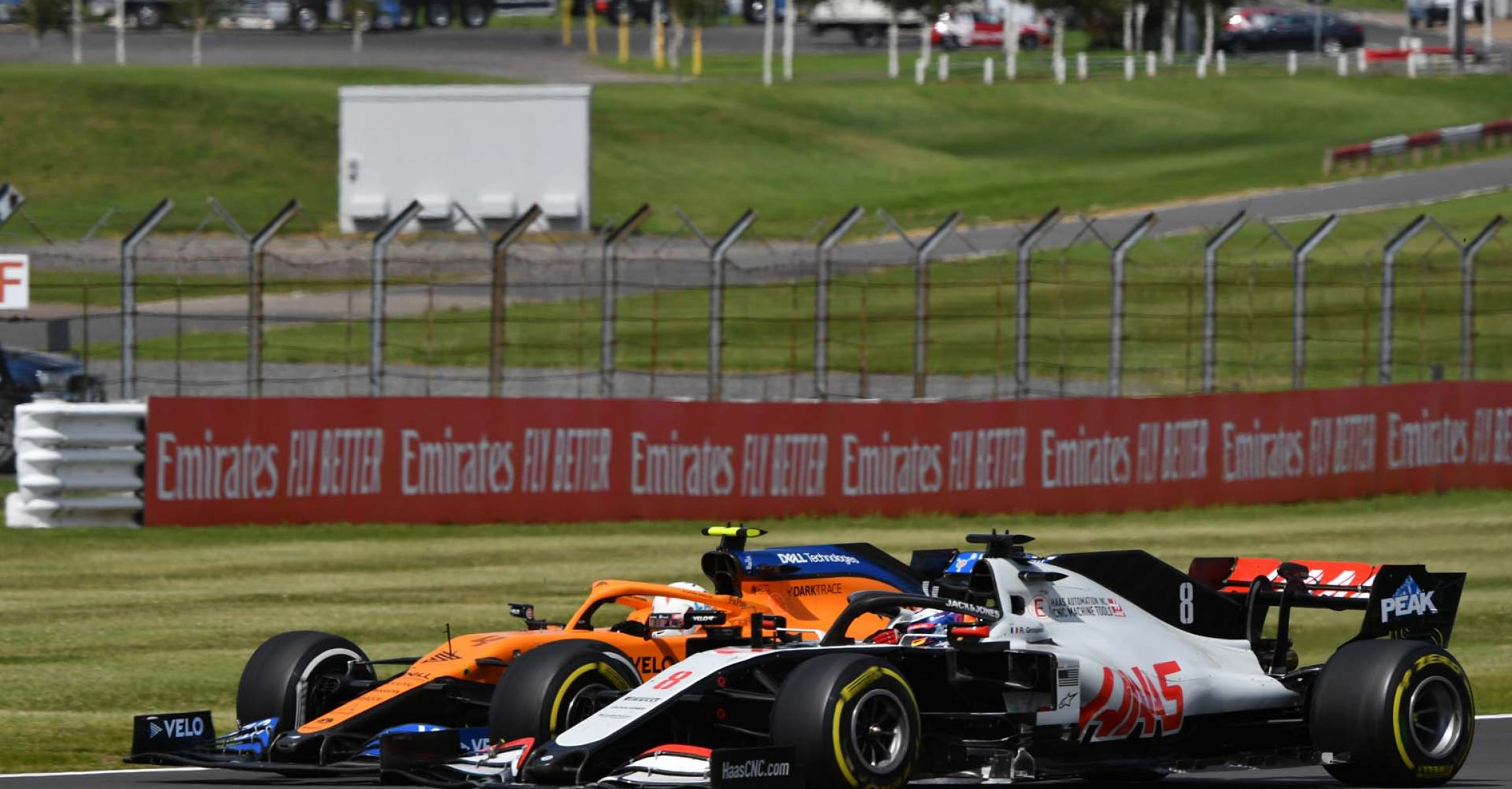 SILVERSTONE, UNITED KINGDOM - AUGUST 02: Lando Norris, McLaren MCL35, battles with Romain Grosjean, Haas VF-20 during the British GP at Silverstone on Sunday August 02, 2020 in Northamptonshire, United Kingdom. (Photo by Mark Sutton / LAT Images)