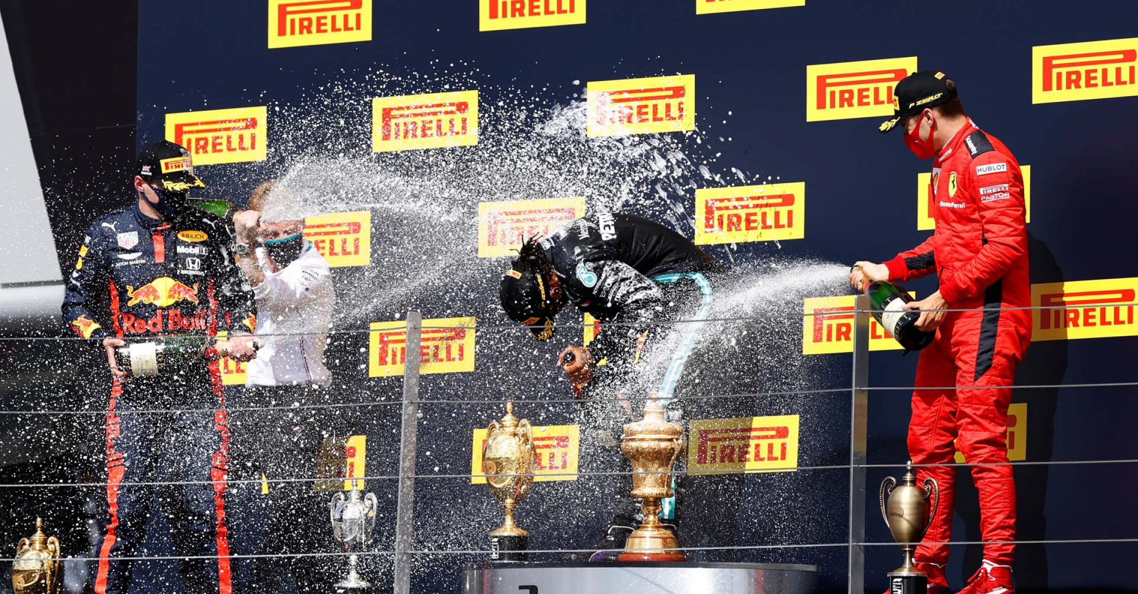 NORTHAMPTON, ENGLAND - AUGUST 02: Race winner Lewis Hamilton of Great Britain and Mercedes GP (C), runner-up Max Verstappen of Netherlands and Red Bull Racing (L) and third-placed Charles Leclerc of Monaco and Ferrari (R) celebrate on the podium during the F1 Grand Prix of Great Britain at Silverstone on August 02, 2020 in Northampton, England. (Photo by Andrew Boyers/Pool via Getty Images) // Getty Images / Red Bull Content Pool  // AP-24TQHBWB92111 // Usage for editorial use only //