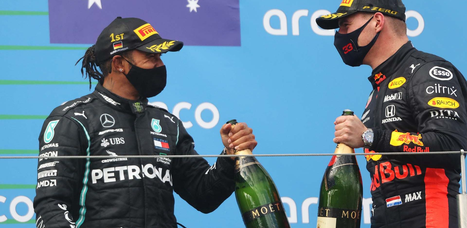 NUERBURG, GERMANY - OCTOBER 11: Race winner Lewis Hamilton of Great Britain and Mercedes GP and second placed Max Verstappen of Netherlands and Red Bull Racing celebrate on the podium during the F1 Eifel Grand Prix at Nuerburgring on October 11, 2020 in Nuerburg, Germany. (Photo by Wolfgang Rattay - Pool/Getty Images)