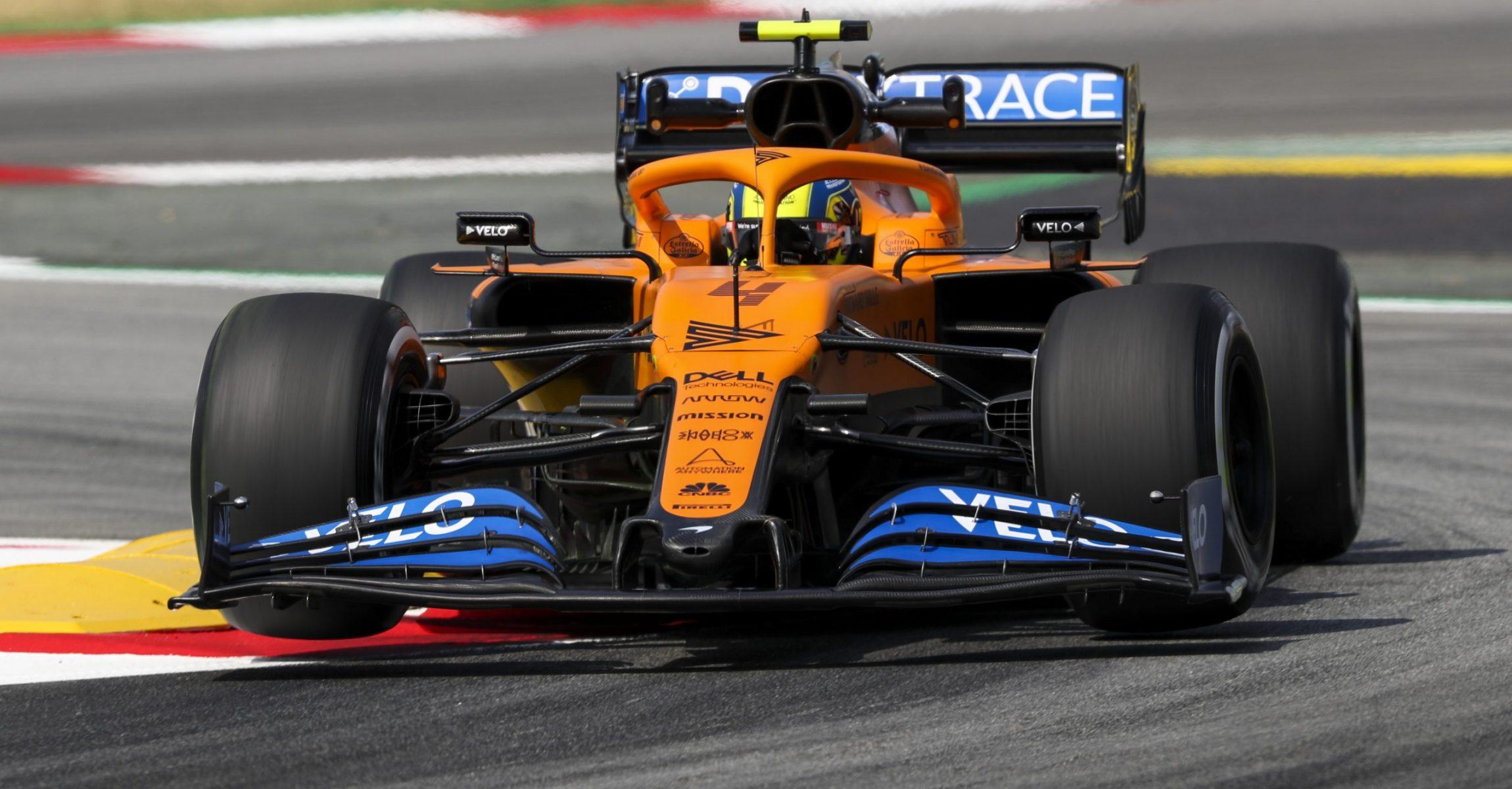 Lando Norris, McLaren MCL35, bounces over a kerb in a chicane