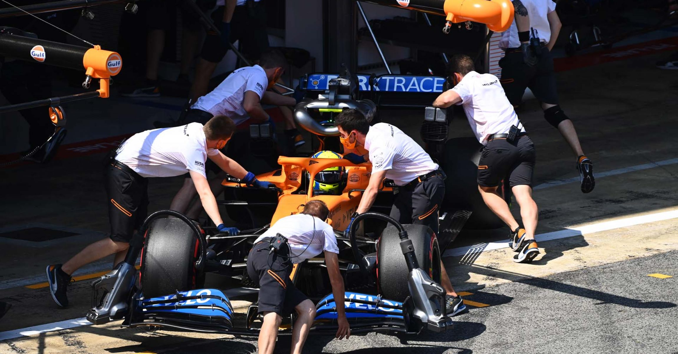 Lando Norris, McLaren MCL35, is returned to the garage. Mechanics wheel the car backwards