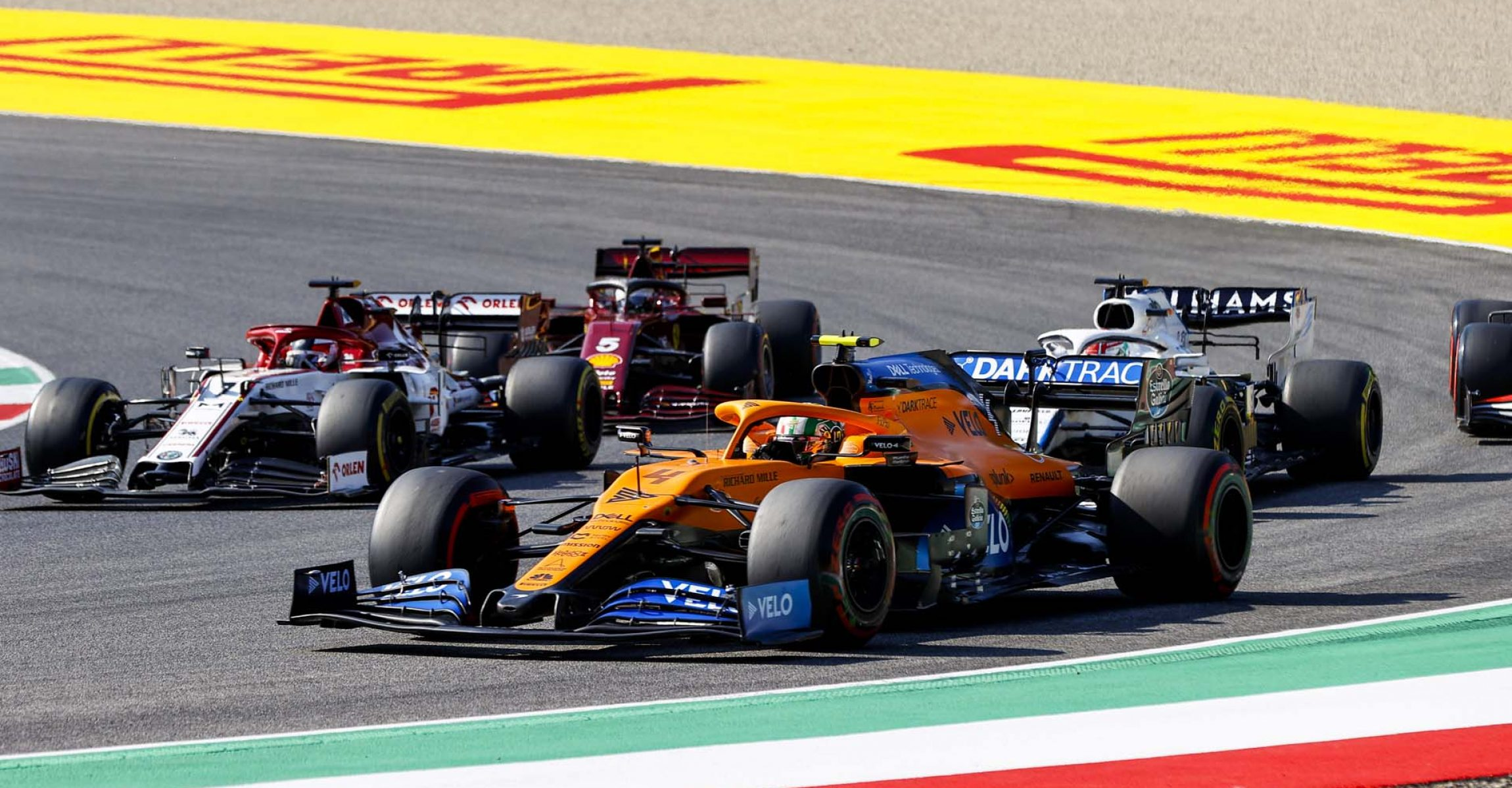 Lando Norris, McLaren MCL35, leads Kimi Raikkonen, Alfa Romeo Racing C39, George Russell, Williams FW43, and Sebastian Vettel, Ferrari SF1000 in a corner
