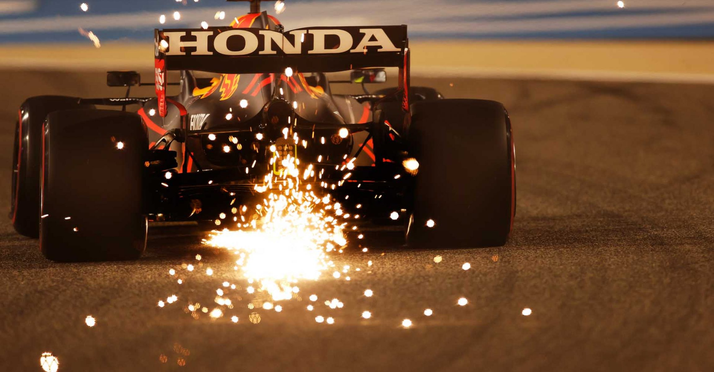 BAHRAIN, BAHRAIN - MARCH 26: Sparks fly behind Sergio Perez of Mexico driving the (11) Red Bull Racing RB16B Honda during practice ahead of the F1 Grand Prix of Bahrain at Bahrain International Circuit on March 26, 2021 in Bahrain, Bahrain. (Photo by Lars Baron/Getty Images)