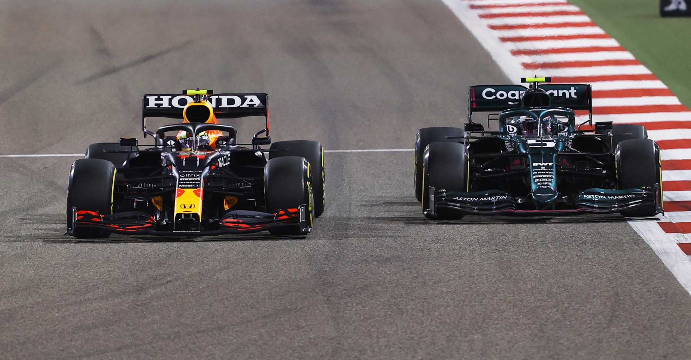 BAHRAIN, BAHRAIN - MARCH 28: Sergio Perez of Mexico driving the (11) Red Bull Racing RB16B Honda and Sebastian Vettel of Germany driving the (5) Aston Martin AMR21 Mercedes compete for position on track during the F1 Grand Prix of Bahrain at Bahrain International Circuit on March 28, 2021 in Bahrain, Bahrain. (Photo by Bryn Lennon/Getty Images)