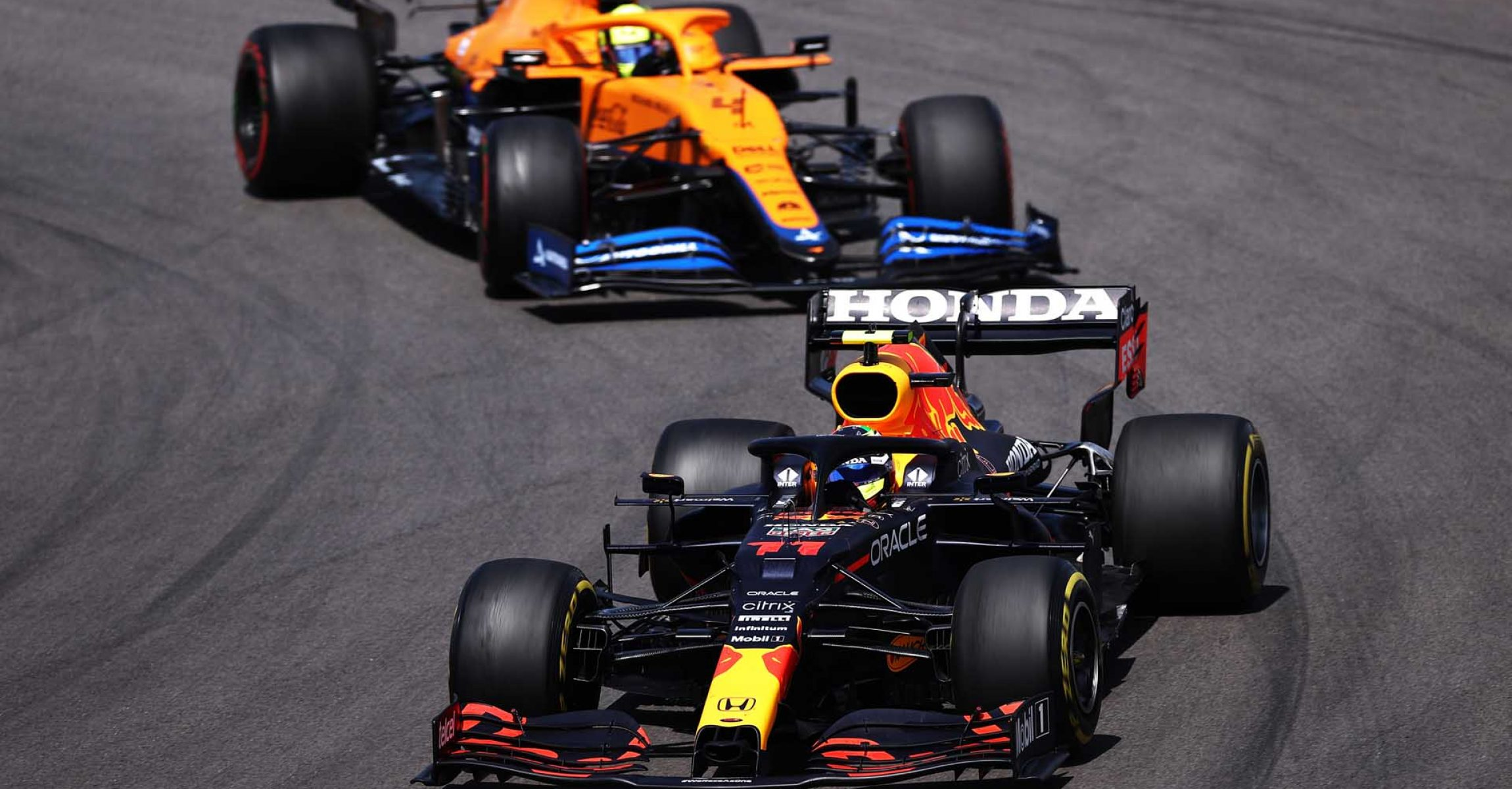 PORTIMAO, PORTUGAL - MAY 02: Sergio Perez of Mexico driving the (11) Red Bull Racing RB16B Honda leads Lando Norris of Great Britain driving the (4) McLaren F1 Team MCL35M Mercedes on track during the F1 Grand Prix of Portugal at Autodromo Internacional Do Algarve on May 02, 2021 in Portimao, Portugal. (Photo by Lars Baron/Getty Images)