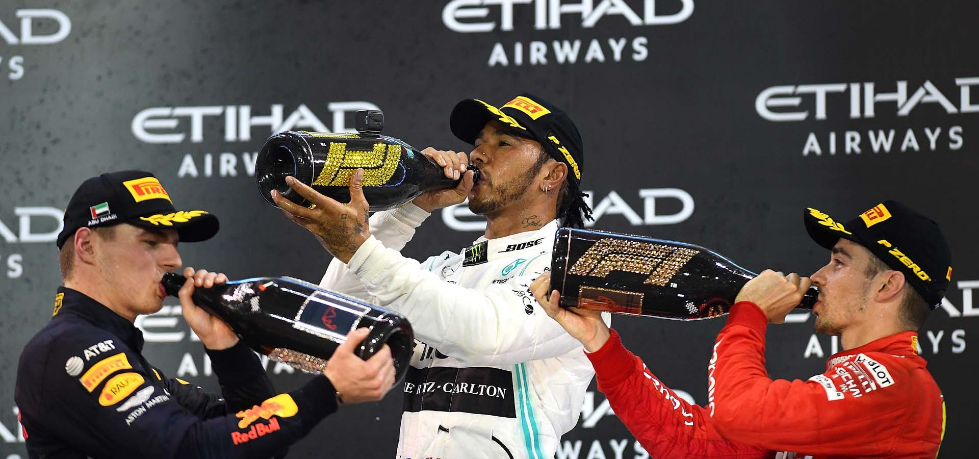 ABU DHABI, UNITED ARAB EMIRATES - DECEMBER 01: Top three finishers Lewis Hamilton of Great Britain and Mercedes GP, Max Verstappen of Netherlands and Red Bull Racing and Charles Leclerc of Monaco and Ferrari celebrate on the podium during the F1 Grand Prix of Abu Dhabi at Yas Marina Circuit on December 01, 2019 in Abu Dhabi, United Arab Emirates. (Photo by Clive Mason/Getty Images) // Getty Images / Red Bull Content Pool  // AP-22BV9XWW12111 // Usage for editorial use only //
