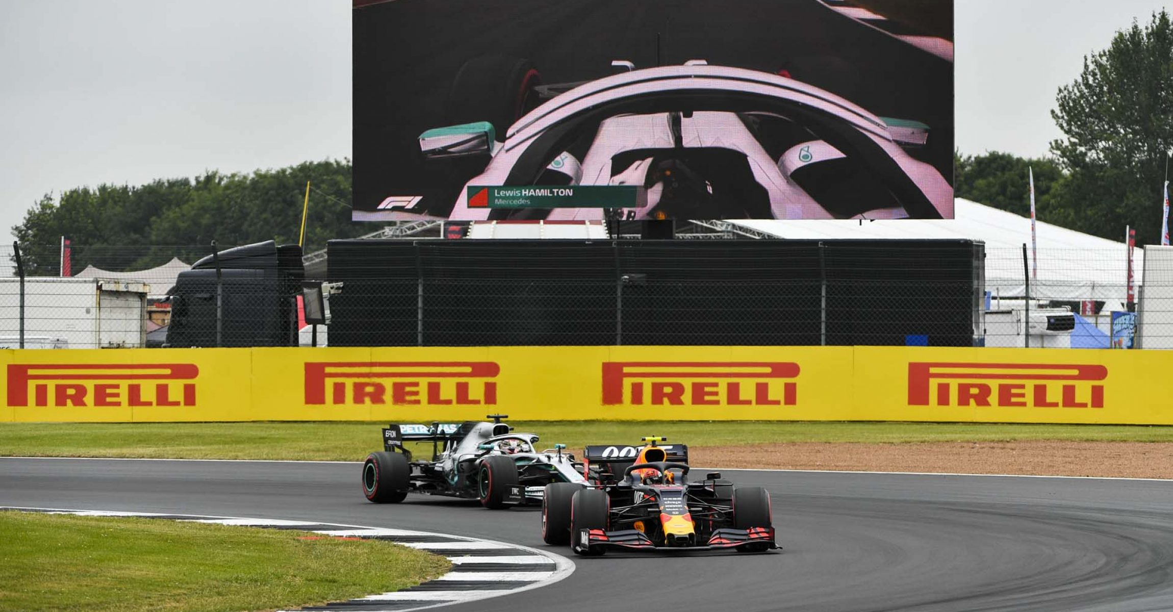 SILVERSTONE, UNITED KINGDOM - JULY 13: Pierre Gasly, Red Bull Racing RB15, leads Lewis Hamilton, Mercedes AMG F1 W10 during the British GP at Silverstone on July 13, 2019 in Silverstone, United Kingdom. (Photo by Mark Sutton / LAT Images)