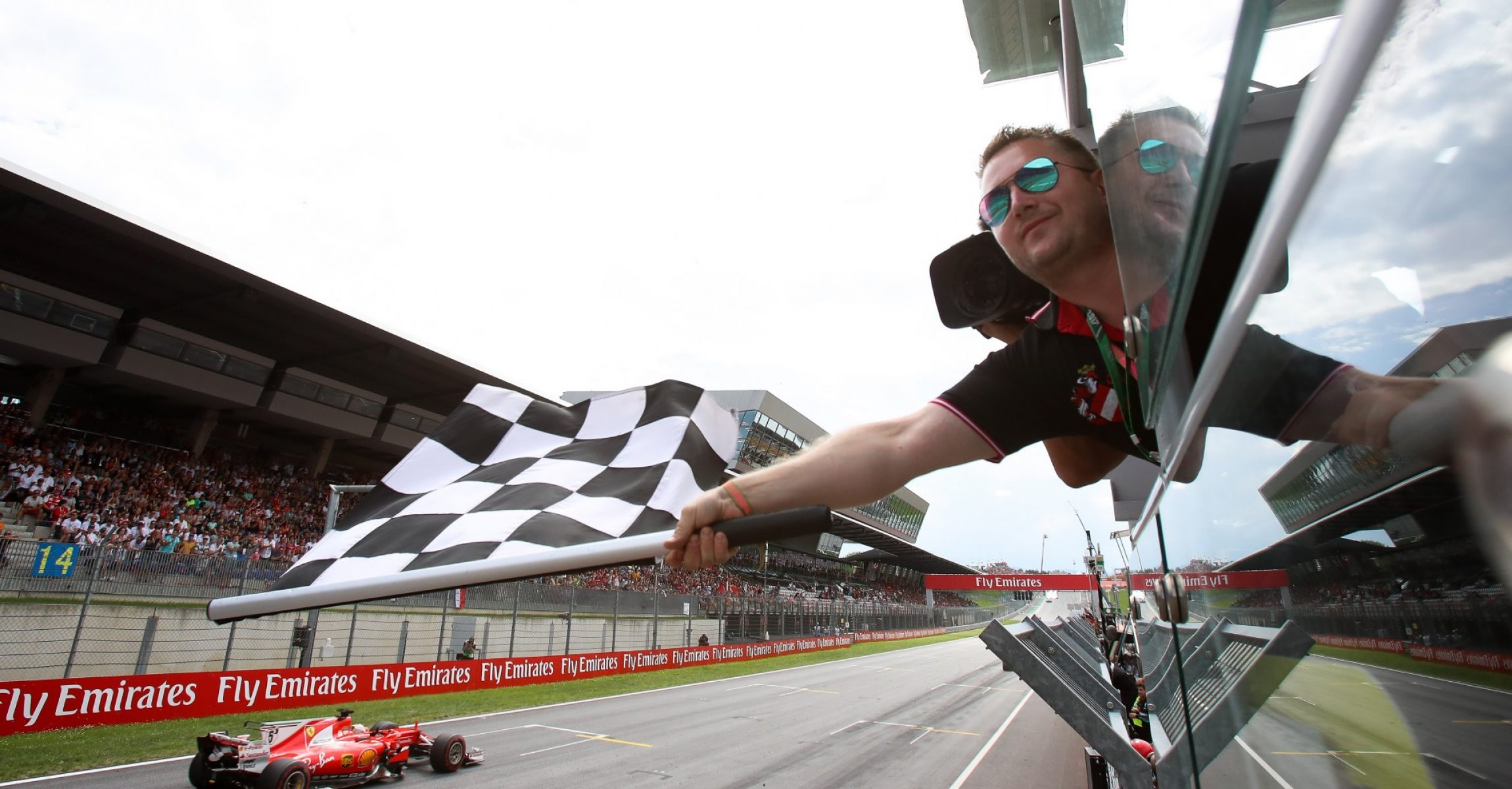 SPIELBERG,AUSTRIA,09.JUL.17 - MOTORSPORTS, FORMULA 1 - Grand Prix of Austria, Red Bull Ring, award ceremony. Image shows the flagman with the chequered flag and Sebastian Vettel (GER/ Ferrari). Photo: GEPA pictures/ Christian Walgram - For editorial use only. Image is free of charge.