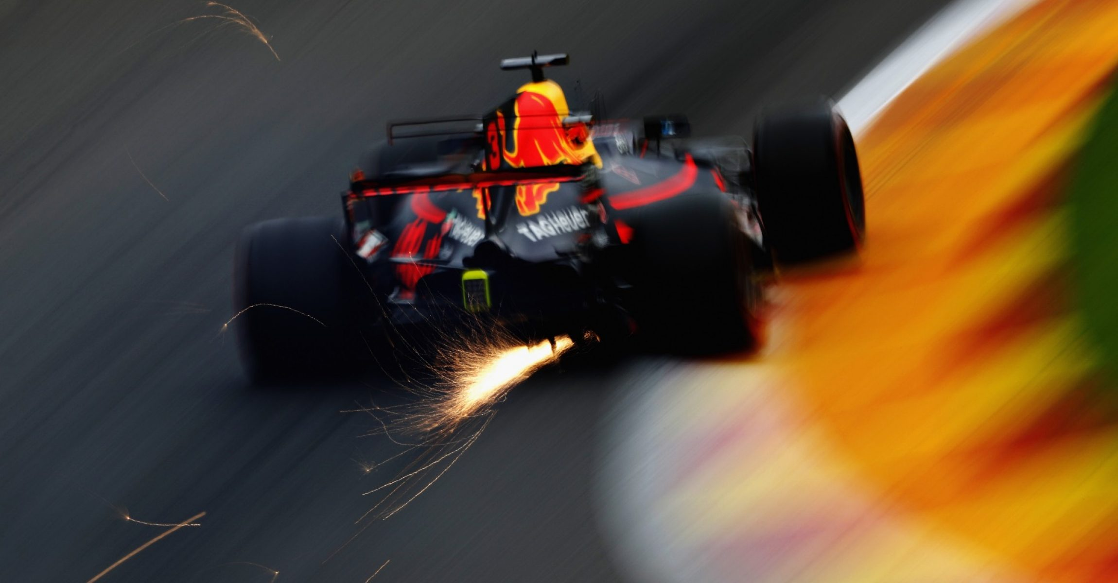 SPA, BELGIUM - AUGUST 25: Sparks fly behind Daniel Ricciardo of Australia driving the (3) Red Bull Racing Red Bull-TAG Heuer RB13 TAG Heuer on track during practice for the Formula One Grand Prix of Belgium at Circuit de Spa-Francorchamps on August 25, 2017 in Spa, Belgium.  (Photo by Mark Thompson/Getty Images)