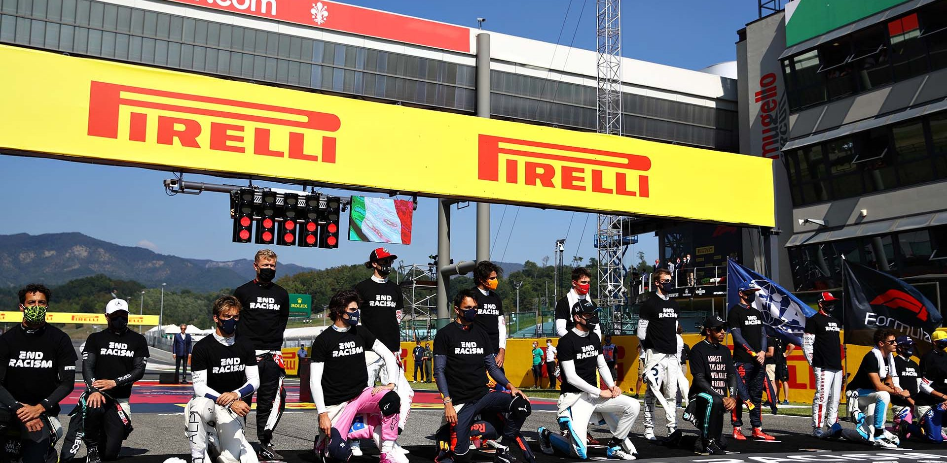 SCARPERIA, ITALY - SEPTEMBER 13: F1 drivers including Pierre Gasly of France and Scuderia AlphaTauri and Alexander Albon of Thailand and Red Bull Racing stand and kneel on the grid in support of ending racism before the F1 Grand Prix of Tuscany at Mugello Circuit on September 13, 2020 in Scarperia, Italy. (Photo by Mark Thompson/Getty Images)