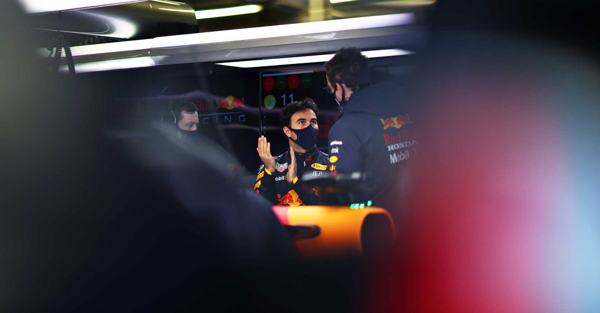 NORTHAMPTON, ENGLAND - FEBRUARY 24: Sergio Perez of Mexico and Red Bull Racing talks with his engineer in the garage during the Red Bull Racing Filming Day at Silverstone on February 24, 2021 in Northampton, England. (Photo by Dan Istitene/Getty Images for Red Bull Racing)