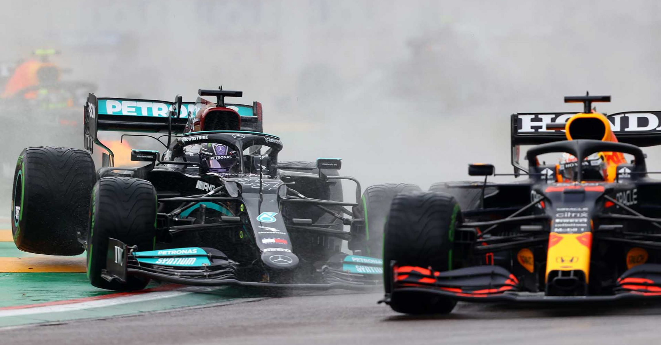 IMOLA, ITALY - APRIL 18: Max Verstappen of the Netherlands driving the (33) Red Bull Racing RB16B Honda and Lewis Hamilton of Great Britain driving the (44) Mercedes AMG Petronas F1 Team Mercedes W12 battle for track position at the start during the F1 Grand Prix of Emilia Romagna at Autodromo Enzo e Dino Ferrari on April 18, 2021 in Imola, Italy. (Photo by Bryn Lennon/Getty Images)